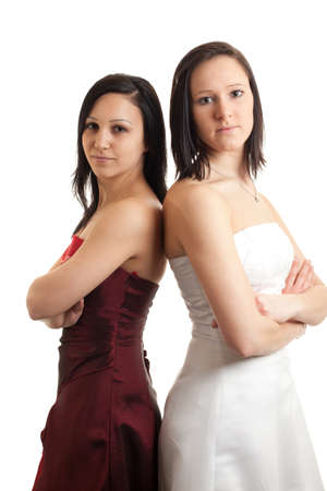 two young women in dresses standing back on back