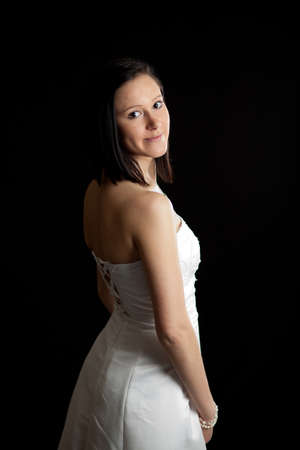 a young woman in a white dress looking backward over her shoulder