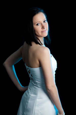 a young woman in a white dress looking backward over her shoulder lit by blue backlight Stock Photo