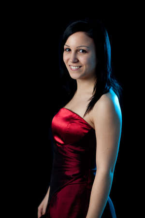 portrait of a young woman in a red dress lit by blue backlight