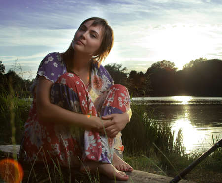 a young woman sitting on a log in front of a lake backlight from the sun lightened up with flash