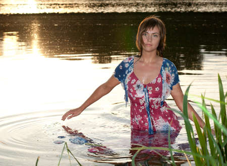 a young woman standing in the water reflections from the sun lightened up with flash Stock Photo