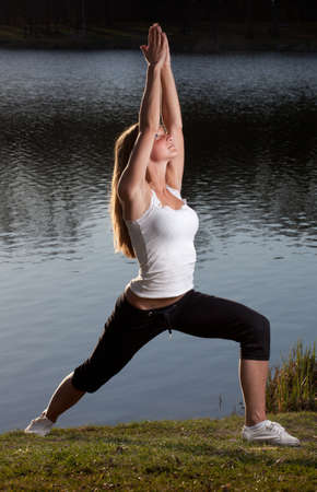 a young woman in a yoga stance in front of a lake