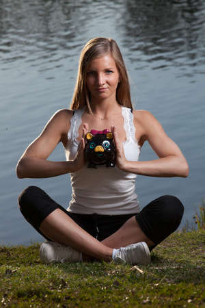 a young woman with a piggy bank meditating in front of a lake photo