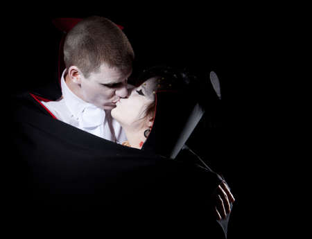 a vampire couple holding each other and kissing photo