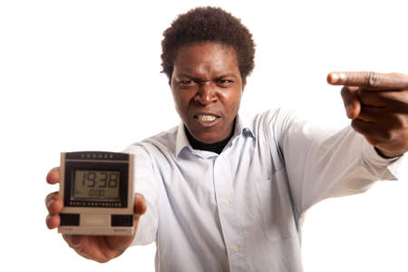 a young man looking angry pointing on a clock
