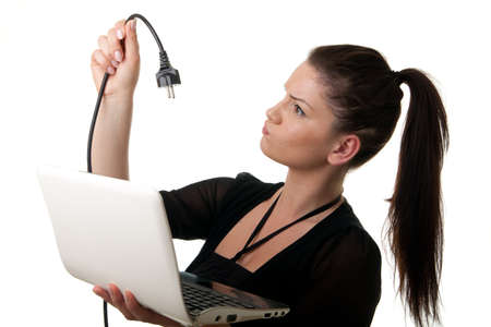 sceptical: a young woman holding a notebook looking at a power cord Stock Photo