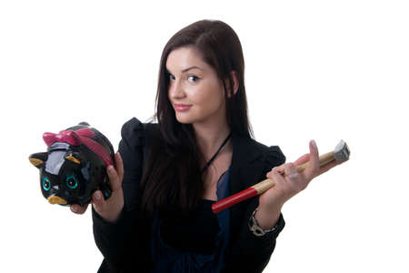 coinbank: a young woman holding a piggy bank and a hammer looking unsure Stock Photo