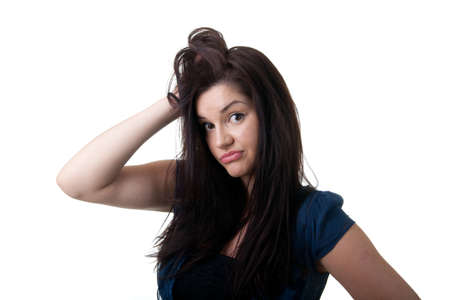 a clueless looking young woman with her hand in her hair Stock Photo