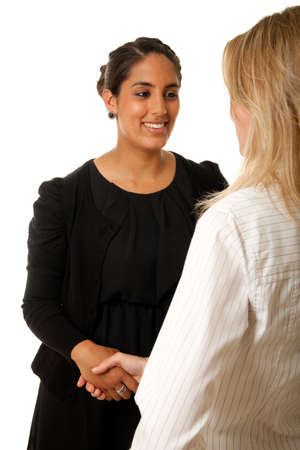 an indian woman shaking the hand of another blonde woman