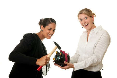 two young women breaking a piggybank with a hammer Stock Photo