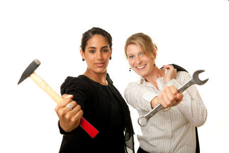 two young businesswoman showing hammer and wrench as tools Stock Photo