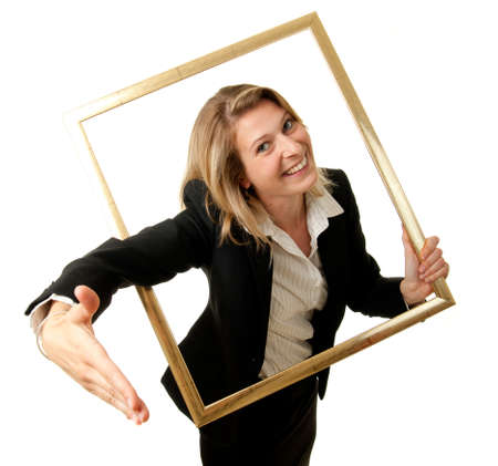 conclude: a young businesswoman offering her hand to conclude a contract through a pictureframe