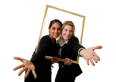 a young indian and a young european businesswoman stretching their hands through a pictureframe photo