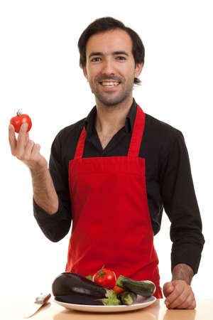 a chef with a plate of vegetables in front of him holding a tomatoe