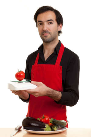 a chef weighing a tomatoe with a kitchen scale Stock Photo