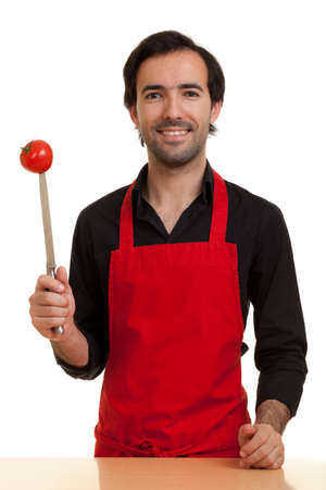 a chef showing a tomatoe pierced with the tip of a kitchen knife Stock Photo