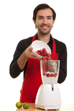 a chef pouring some strawberries into a blender Stock Photo