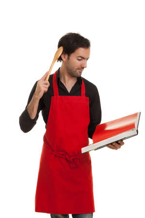 aprons: a thinking chef reading in a cookbook scratching his head with a spoon Stock Photo
