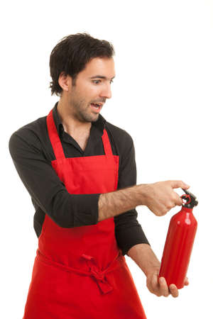 a profile shot of a scared looking chef with a fire extinguisher