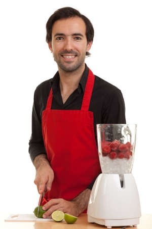 a chef with a blender in front of him cutting a lime with a kitchen knife Stock Photo