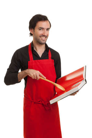 a smiling chef looking at the camera and pointing to a cookbook with a spoon Stock Photo