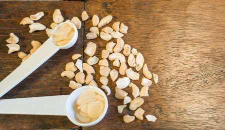 measuring spoon: A pile of sliced almond in the measuring spoon show on the left prepared to make bakery with cashews decoration Stock Photo