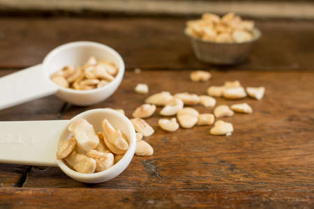 measuring spoon: a pile of cashew in the measuring spoon focusing on teaspoon show on the left prepared to make bakery Stock Photo