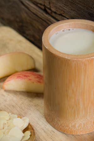 leche de soya: El desayuno dieta - una taza de leche de soja en la placa de madera Flaten centr�ndose en la copa de leche de soya Foto de archivo