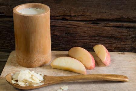 leche de soya: El desayuno dieta - una taza de leche de soja en la placa Flaten de madera decorado con almendras en rodajas