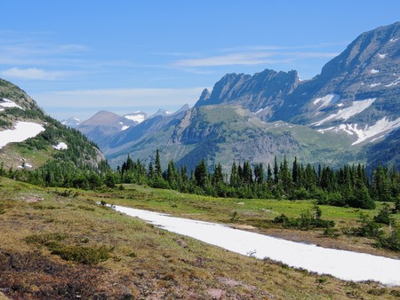 Going to the Sun Road, View of Landscape, snow fields In Glacier National Park around Logan Pass, Hidden Lake, Highline Trail, which features waterfalls, wildlife, and is surrounded by mountains including: Piegan, Pollock, Oberlin, Clements, Reynolds and Heavy Runner Mountain Montana USA Stock Photo