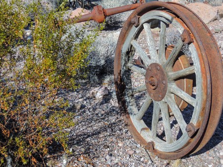 Old metal Wagon wheels rusting on the ground among jumping cactus in the Arizona desert in deserted ghost mining town.