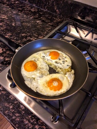 Three Organic Chicken Eggs frying in pan on gas stove with granite countertops. Banco de Imagens