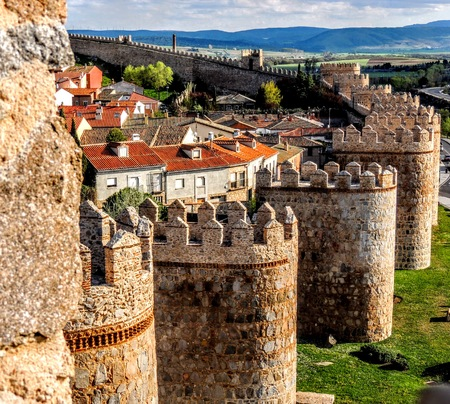 Wall Tower Bastion Avila Spain Made Yellow Stone Bricks with view of town and countryside with clouds and mountains in the background