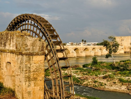 Ruins of an ancient arabic mill in Cordoba, Andalusia, Spain with old working bridge in background