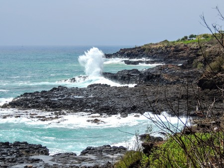 Lava Rock and Coral with Spray of crashing waves in beach tide pools at Beach in Kauai Hawaii with sky and clouds