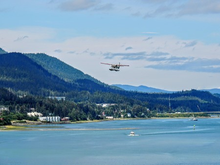 White Float Pontoon Seaplane Taking off from Juneau Harbor with boats and city in background Archivio Fotografico - 96753777