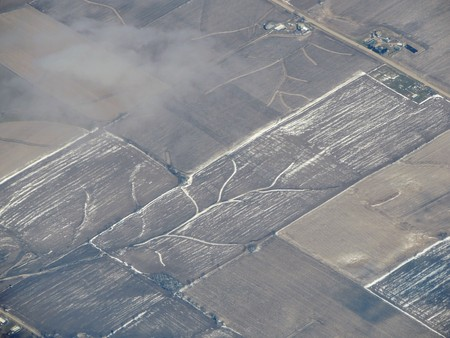 Aerial winter snow landscape view of rural and city land between Minneapolis Minnesota and Indianapolis Indiana with stark contrast between snow covered fields, hills and riverbeds. Stock Photo