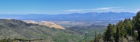 Panoramic view of Wasatch Front Rocky Mountains from the Oquirrh Mountains, by Kennecott Rio Tinto Copper mine, Utah Lake and Great Salt Lake Valley in early spring with melting snow and Cloudscape. Utah, USA.