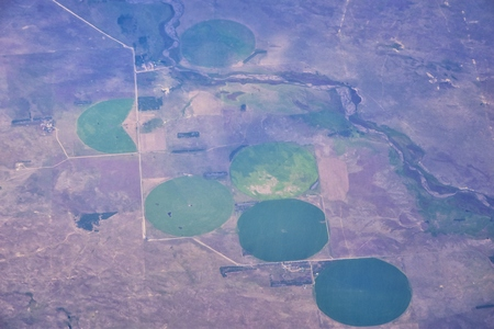 Aerial view of crop circles and squares over midwest states on flight over Colorado, Kansas, Missouri, Illinois, Indiana, Ohio and West Virginia during autumn. Grand sweeping views of agriculture landscape. Views of crops, rivers, plains, mountain and landscape patterns. Top view, USA.