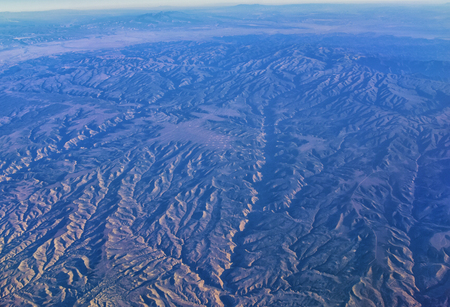 Aerial view of topographical Rocky Mountain landscapes on flight over Colorado and Utah during autumn. Grand sweeping views of rivers, mountain and landscape patterns. Top view, Rockies and Wasatch Front, USA.