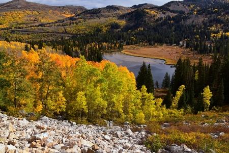 Silver Lake bij Solitude en Brighton Skiresort in Big Cottonwood Canyon. Panoramisch uitzicht vanaf de wandel- en promenadepaden van de omliggende bergen, espen- en pijnbomen in schitterende herfstkleuren. In de Rocky Mountains, Wasatch Front, Utah, VS. Stockfoto