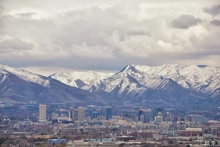 Downtown Salt Lake City Panoramablick auf die Wasatch Front Rocky Mountains vom Flugzeug im frühen Frühlingswinter mit schmelzendem Schnee und Wolkengebilde. Utah, USA. Standard-Bild