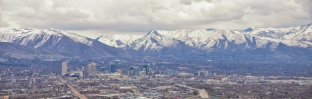 Downtown Salt Lake City Panoramic view of Wasatch Front Rocky Mountains from airplane in early spring winter with melting snow and cloudscape. Utah, USA.