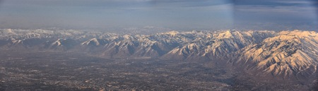 Aerial view from airplane of the Wasatch Front Rocky Mountain Range with snow capped peaks in winter including urban cities of Provo, Farmington Bountiful, Orem and Salt Lake City. Utah. United States.