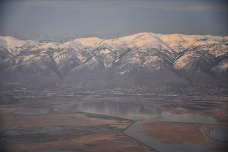 Luftaufnahme vom Flugzeug der Wasatch Front Rocky Mountain Range mit schneebedeckten Gipfeln im Winter, einschließlich der städtischen Städte Provo, Farmington Bountiful, Orem und Salt Lake City. Utah. Vereinigte Staaten.