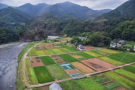 Rural landscape around Tokyo Japan, views of rice fields, mountains, rivers and farming village from train ride. Asia. 写真素材