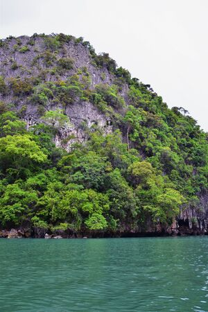 Island, Ocean views near Phuket Thailand with Blues, Turquoise and Greens oceans, mountains, boats, caves, trees resort island of phuket Thailand. Including Phi Phi, Ko Rang Yai, Ko Li Pe and other islands. Asia.