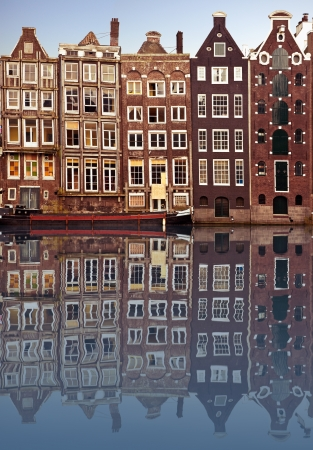 Typical Amsterdam houses reflected in the canal with blue sky background photo