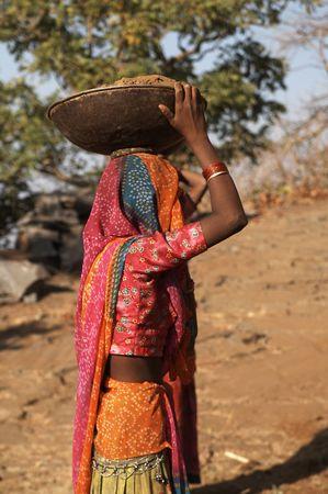 obrero: Mujer india trabajador llevaba colorido sari con una taza de metal lleno de tierra